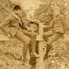 Three unidentified boys. Two sit on a fence